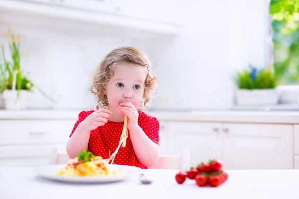40759607 - kids eat pasta. healthy lunch for children. toddler kid eating spaghetti bolognese in a white kitchen at home. preschooler child cooking noodles with tomato and pepper for dinner. food for family.