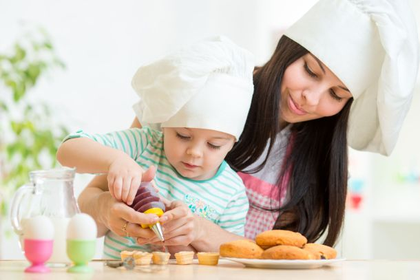 33576415 - mother and little girl making cookies together at kitchen