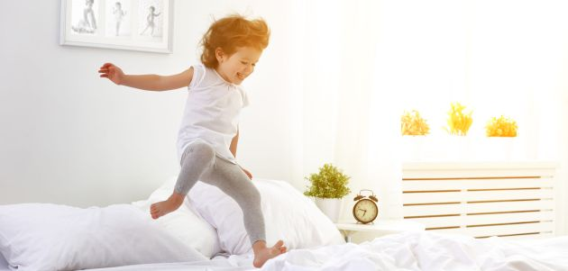 53529668 - happy child girl having fun jumps and plays bed